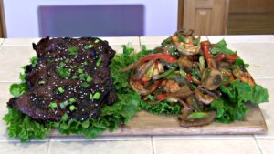 SmokingPit.com - Sesame Soy thin  sliced Beef Bottom Round Steak with a shrimp stirfry. Beef is cooked on a Santa Maria style  grill. Stir fry is done on a Wok in the grill. -  The money shot.